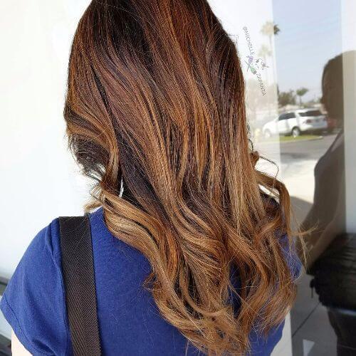 dark caramel brown hair styled in long waves