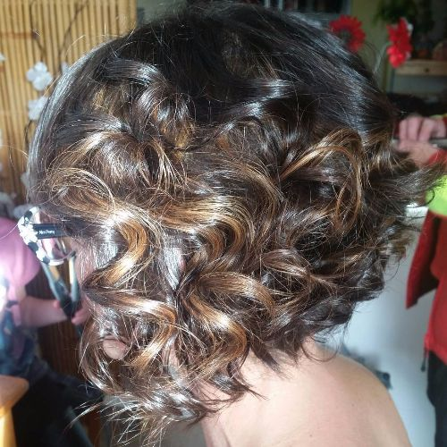 curly caramel highlights on dark hair