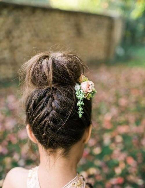 Bun with a french braid in the back and floral hair accessories bridesmaids hairstyles