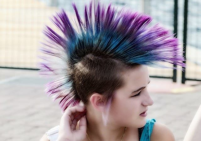 a female mohawk hairstyle that is spiky and colored purple